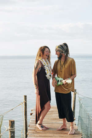 Man playing ukulele and singing for his beautiful happy wife when they are spending honeymoon by sea