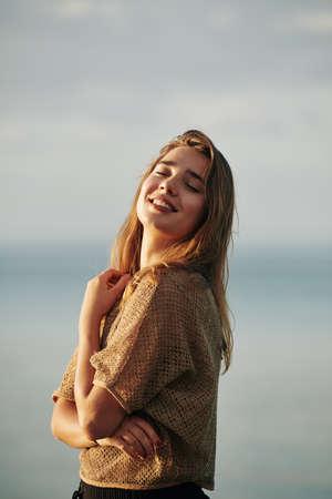 Portrait of young beautiful woman enjoying sea breeze and sunset sun rays