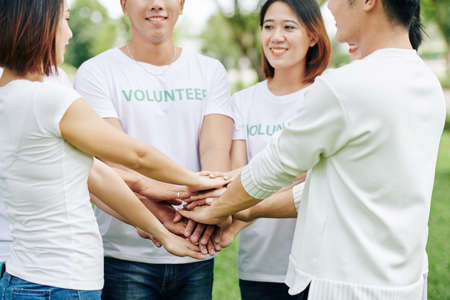 Group of volunteers stacking hands before enthusiastically engage in cleaning activity in local park