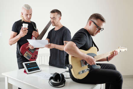 Songwriter giving document with notes and lyrics to gitar player at rehearsal