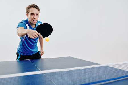 Young sportsman playing table tennis at competition and hitting the ball back