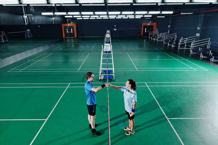 Young male and female badminton players shaking hands after training in gymnasium