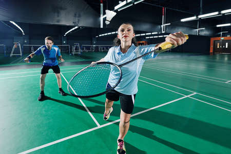 Concentrated couple playing badminton in team in gymnasium