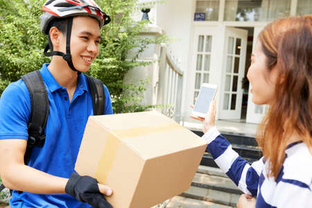 Young woman telling delivery man that she is paying for shipping with banking application
