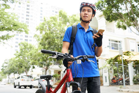 Smiling young Vietnamese man with smartphone walking next to his bicycle and searching for cirtain building