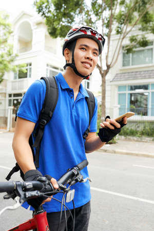 Smiling young Asian courier with smartphone in hand searching for delivery address