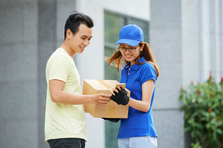 Courier and customer checking delivery details in mobile application