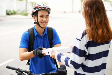 Smiling handsome young delivery man giving box of pizza to female customer