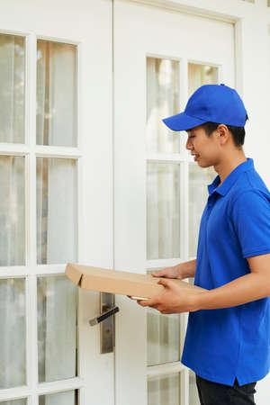 Delivery man in blue uniform bringing package to entrance doors of customer Reklamní fotografie