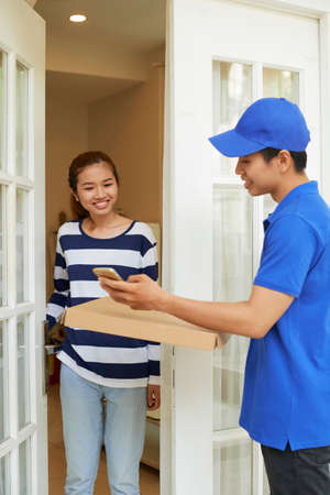 Mobile delivery servce representative in blue uniform bringing package to young woman