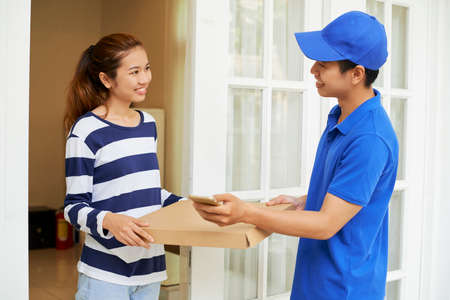 Happy young pretty Asian woman receiving pizza she ordered online Stock Photo