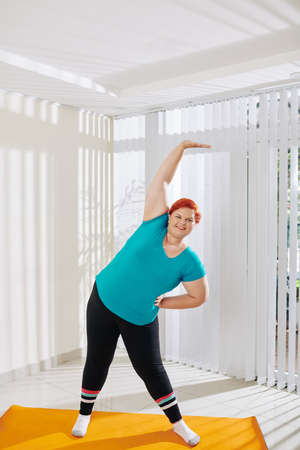 Smiling pretty young overweight woman doing side bends when exersizing at health center