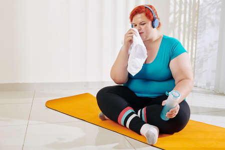 Young overweight woman wiping face and drinking fresh water after training at health club