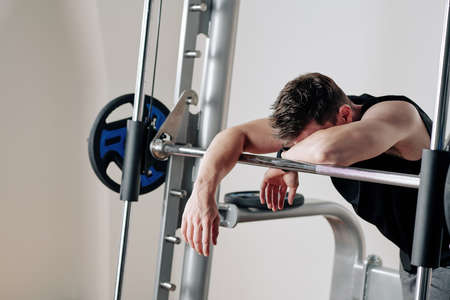 Tired young bodybuilder leaning on barbell after lifting heavy weights in gym