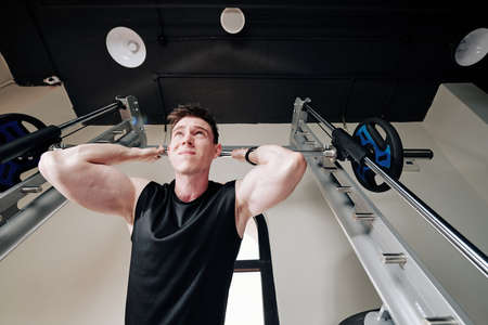 Concentrated strong young sportsman lifting heavy barbell in gym