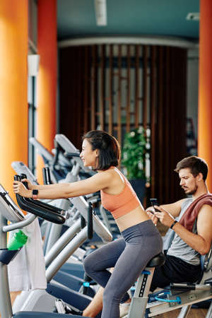 Smiling pretty young Asian woman training at fitness center and riding stationary bike