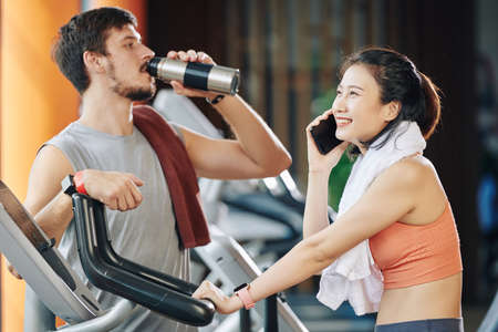 Cheerful young Vietnamese woman talking on phone when riding stationary bike, her trainer standing near by and drinking fresh water