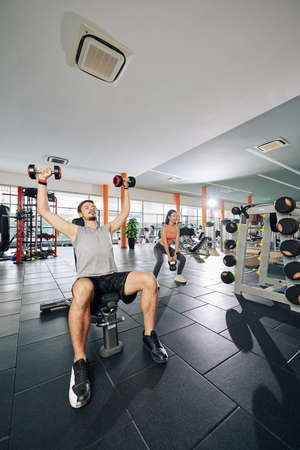 People exercising with heavy weights in gym, young woman doing squats when man lifting dumbbells Zdjęcie Seryjne