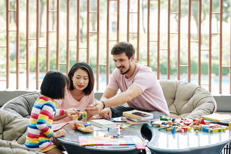 Cheerful multi-ethnic parents playing with little daughter, giving her puzzle toys and bricks Reklamní fotografie