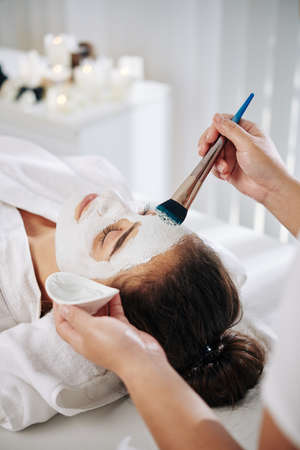 Young woman getting beauty treatment in spa salon and enjoying soothing mask