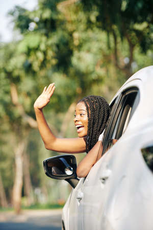 Excited young Black woman sticking out of car window and waving with hand to attract attention of friend 免版税图像