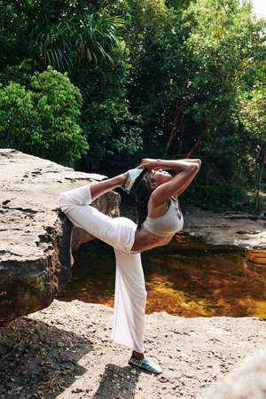 Flexible woman doing advanced yoga backbends when standing on rock in forest