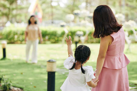 Little girl holding hand of her mother and waving with hand to grandmother in background