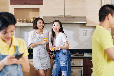 Pretty young Vietnamese women having drinks and gossiping at house party