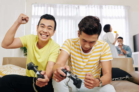 Happy Asian guy celebrating his victory in video game while his friend is frustrated after loosing