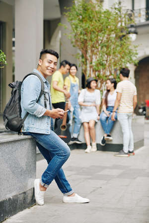 Handsome Asian university student standing at university campus and texting friends