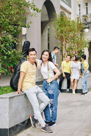 Cheerful Vietnamese college students standing at campus entrance and looking at camera