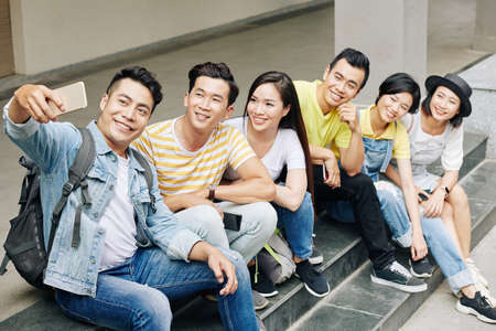Cheerful Vietnamese university student taking selfie with friends sitting on steps