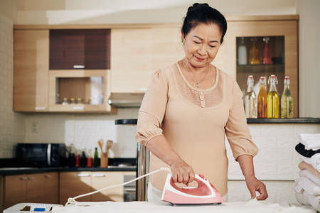 Smiling senior Asian woman ironing clothes at home during pandemic period when she needs to stay at home Stock Photo