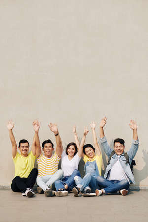 Group of happy excited young Asian people sitting at the wall and raising arms