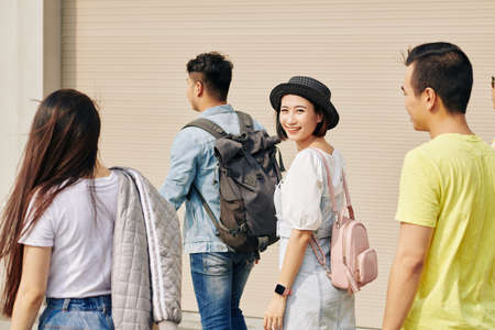 Beautiful young Vietnamese woman in small hat walking to university class Stockfoto