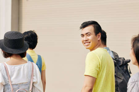 Positive young Asian man in simple yellow t-shirt going to college