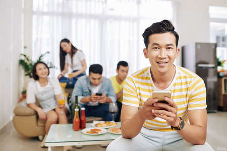 Smiling Vietnamese young man texting and looking at camera when his friends eating and drinking in background at house party