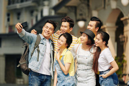 Happy Vietnamese young man taking selfie with group of friends when standing in the street