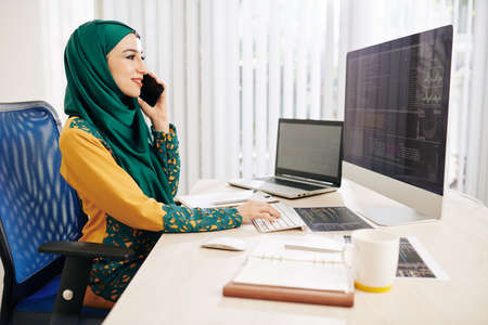 Smiling young muslim software developer talking on phone when checking programming code on computer screen