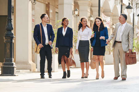 Pretty young busineswoman telling funny joke to her colleagues when they are walking in the street after meeting