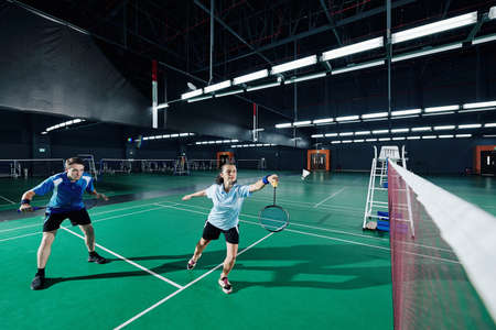 Mixed double playing badminton game, woman jumping and swinging racket to beat off shuttlecock