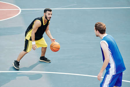 Multi-ethnic young men playing basketball on outdoor court