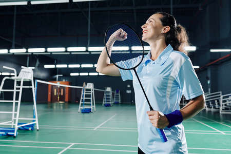 Excited happy young female badminton player making fist bump when celebrating victory