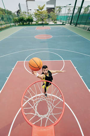 Basketball player jumping and throwing ball in basket, view from above