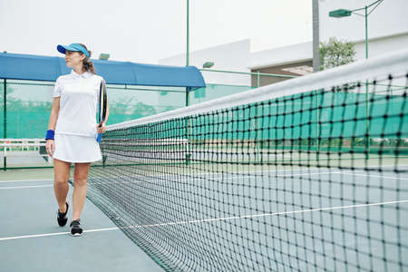 Smiling young female outdoor tennis player walking along stretched net