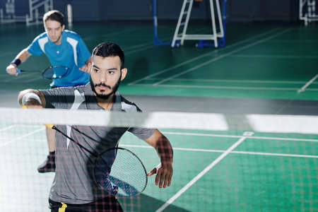 Multi-ethnic pair of badminton players taking part in competition