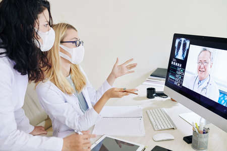 Young doctors in medical masks having video conference with experienced pulmonologist and discussing symptoms of coronavirus
