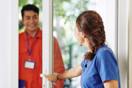 Woman opening entrance door to let in a service worker