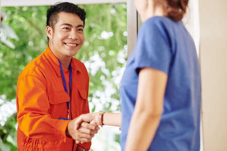 Smiling handsome Asian service worker shaking hand of female customer opening house door
