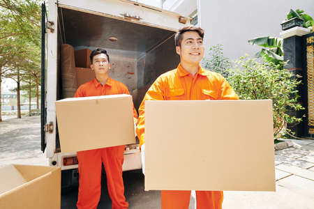 Positive Vietnamese moving service workers in orange uniform carrying cardboard boxes to house entrance Reklamní fotografie - 144565947